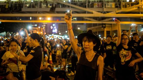 A protester waves her cell phone in the air outside the Hong Kong Government Complex on October 1.