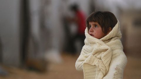 A Syrian refugee wraps herself in a blanket as she stands near tents near Sanliurfa, Turkey, on Thursday, October 2.