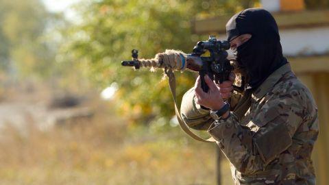 An Ukrainian sniper aims his weapon at a checkpoint near Popasna, Ukraine, on Thursday, October 2.