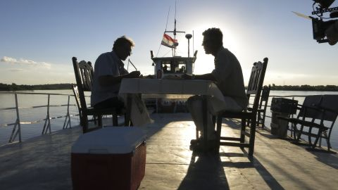 Bourdain and Peter, a German expat, sit down to dinner on the deck of the Cacique II at sunset as it steams up the Paraguay River.