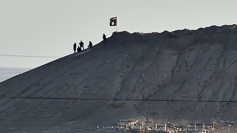 Alleged ISIS militants stand next to an ISIS flag atop a hill in Kobani on Monday, October 6.