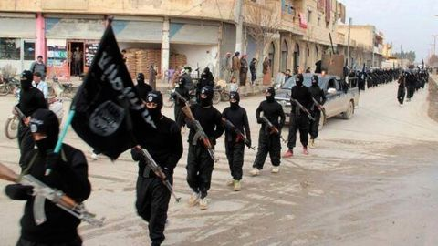 [File] This undated image shows ISIS fighters marching through Raqqa, Syria.