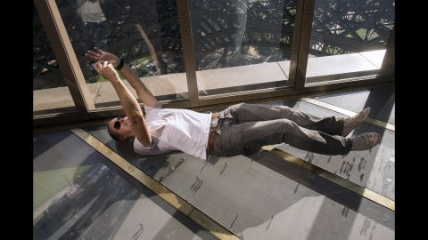 A visitor lies down to take a selfie on the new glass floor of Paris' Eiffel Tower on Friday, October 3. The transparent walkway offers dramatic views 187 feet in the air.