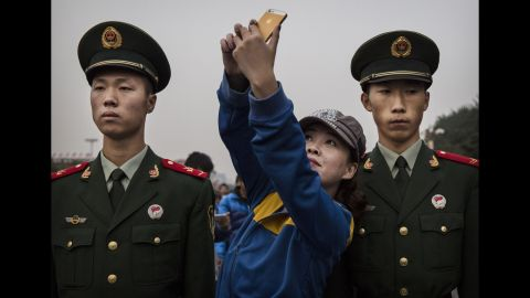 A woman poses for a selfie between two soldiers in Beijing on Wednesday, October 1. It was China's National Day, a holiday that marks the republic's founding.