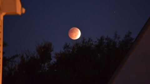 """The lunar eclipse hovers over <a href=""""http://ireport.cnn.com/docs/DOC-1177442"""">Marie Diaz's</a> home in Virginia Beach, Virginia, early Wednesday morning."""