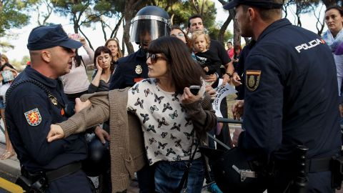 MADRID, SPAIN - OCTOBER 08: Policemen pull from an animal rights protester as a van allegedly containing the dog named Excalibur drove away from an apartment building, the private residence for Spanish nurse Teresa Romero who has tested positive for the Ebola virus on October 8, 2014 in Alcorcon, near Madrid, Spain. Teresa's dog is thought to be at risk of being put down as health officials try to keep the virus from spreading. Spanish Health Minister Ana Mato confirmed nurse, Teresa Romero had tested positive after treating two Ebola patients who had been brought back to the country from Africa. (Photo by Pablo Blazquez Dominguez/Getty Images)