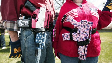 A couple at a Michigan open-carry gun rally celebrates America and the right to bear arms.