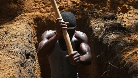 A man digs a grave on October 7, 2014, outside an Ebola treatment center near Gbarnga, Liberia.