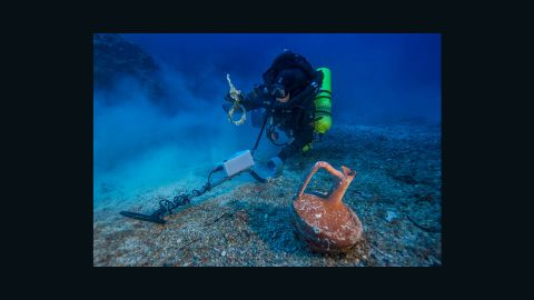 """Greek technical diver Alexandros Sotiriou discovers an intact """"lagynos"""" ceramic table jug and a bronze rigging ring on the Antikythera shipwreck."""