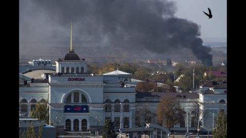 Smoke rises behind the train station in Donetsk, Ukraine, during an artillery battle between pro-Russian rebels and Ukrainian government forces on Sunday, October 12.