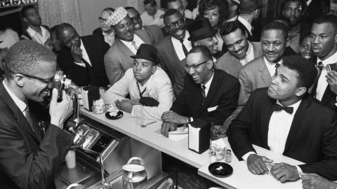 Civil rights activist Malcolm X, left, takes a picture of a tuxedo-clad Ali surrounded by jubilant fans in March 1964. Shortly after the Liston fight, Ali announced that he had joined the Nation of Islam and changed his name from Cassius Clay.