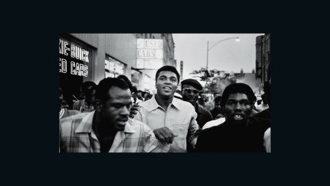 """Ali walks through the streets of New York with members of the Black Panther Party in September 1970. Ali was sentenced to five years in prison for his refusal to enter the draft, and he was also stripped of his boxing title. The U.S. Supreme Court overturned Ali's conviction in 1971, but by that time Ali had already become a figurehead of resistance and a hero to many. <a href=""""http://www.cnn.com/2016/06/02/sport/muhammad-ali-three-days/index.html"""" target=""""_blank"""">Related: Photographer fondly recalls his three days with Ali</a>"""