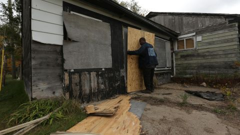 Lory Welch boards up an abandoned home in the 1800 block of East 19th Avenue October 21, 2014 in Gary, Indiana.