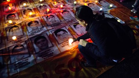 A woman places a candle on photos of the missing students during a protest against the disappearance of 43 students from the Isidro Burgos rural teachers college, in Mexico City, Wednesday, Oct. 22, 2014. Tens of thousands marched in Mexico City's main avenue demanding the return of the missing students. The Mexican government says it still does not know what happened to the young people after they were rounded up by local police in Iguala, a town in southern Mexico, and allegedly handed over to gunmen from a drug cartel Sept. 26, even though authorities have arrested 50 people allegedly involved. They include police officers and alleged members of the Guerreros Unidos cartel. (AP Photo/Eduardo Verdugo)