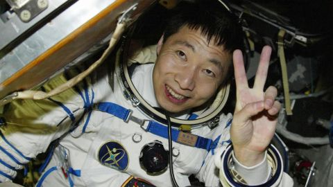 Chinese astronaut Yang Liwei waves from the Shenzhou V capsule after completing China's first manned space flight in 2003.