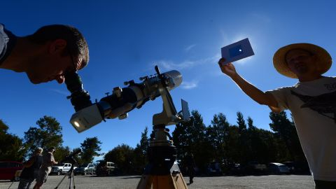 Norm Vargas holds a filter so another person can view the eclipse through a telescope at Mount Wilson Observatory in the San Gabriel Mountains northeast of Los Angeles.