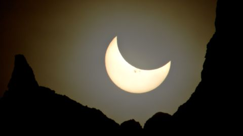 """<a href=""""http://ireport.cnn.com/docs/DOC-1182579"""">John Powell</a> photographed the eclipsed sun, which looked more like a crescent moon, hanging over Badlands National Park in South Dakota."""