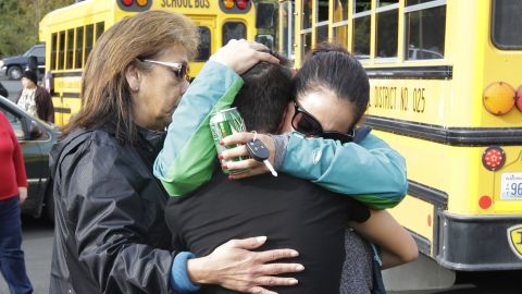 People embrace at the church where students were taken to be reunited with parents.