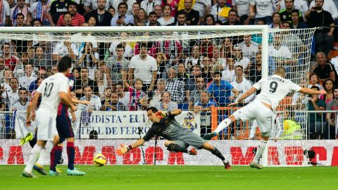 Benzema (right) slides his shot past Cladio Bravo to score Real Madrid's third goal against Barcelona in  a 3-1 win at the Bernabeu in October 2014.