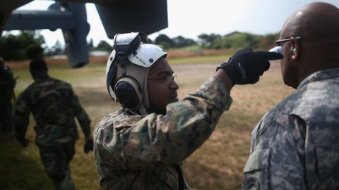 TUBMANBURG, LIBERIA - OCTOBER 15:  A U.S. Marine checks the temperature of Maj. Gen. Darryl Williams, commander of U.S. Army Africa, before boarding an MV-22 Osprey tiltrotor aircraft on October 15, 2014 in Tubmanburg, Liberia. The general visited the site of the first of 17 Ebola treatment centers being constructed by Liberian forces under American supervision as part of Operation United Assistance to combat the Ebola epidemic. (Photo by John Moore/Getty Images)
