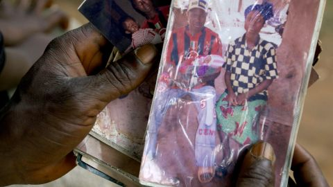 Etienne Ouamouno holds a photo of his wife and son Emile. Researchers think the boy was the outbreak's first victim.