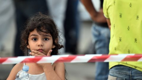 A migrant child disembarks from a coastguard ship in Palermo, Sicily after being rescued on the way across the Mediterranean.