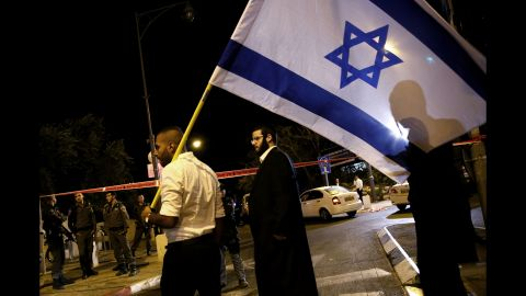 Israeli demonstrators wave flags outside the Menachem Begin Heritage Center, where Glick was shot in Jerusalem on October 29.