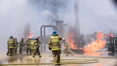 The firefighters at Texas A&M show Rowe how to properly put out a fire.