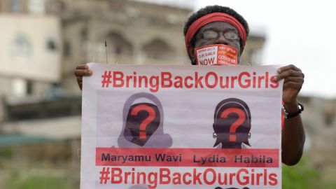 Caption:A supporter of the #BringBackOurGirls campaign carries a placard showing the missing faces of the kidnapped Chibok schoolgirl during a demonstration in the Nigerian capital Abuja on October 14, 2014. Nigerian police on Tuesday blocked supporters of 219 schoolgirls kidnapped by Boko Haram militants from marching on the president's official residence on the six-month anniversary of the abduction. A wall of female officers in full riot gear formed the first line of a barricade in front of less than 100 members of the Bring Back Our Girls campaign, preventing them from setting out.AFP PHOTO/PIUS UTOMI EKPEI (Photo credit should read PIUS UTOMI EKPEI/AFP/Getty Images)