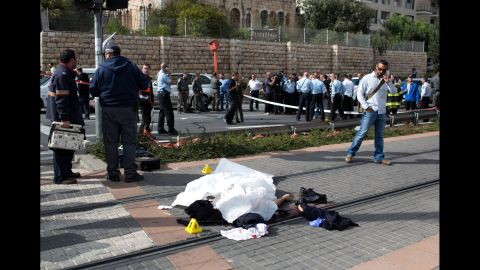 """The body of Palestinian attacker lies covered on the rails of Jerusalem's tramway on November 5, 2014 after he was killed when he deliberately rammed his vehicle into a crowd of pedestrians in Jerusalem. One person was killed and at least nine others wounded. Police described the incident as a """"hit and run terror attack"""" and said it took place in the same area as a similar attack two weeks ago, in which a Palestinian rammed a car into a crowd killing a woman and a baby.  AFP PHOTO/MENAHEM KAHANA        (Photo credit should read MENAHEM KAHANA/AFP/Getty Images)"""