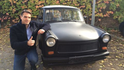 CNN's Frederik Pleitgen poses next to a Trabant, before it was painted and signed by thousands. The vehicle has been an icon to Germans ever since the tiny Communist-built cars started rolling across the border between what was then East and West Germany in 1989.
