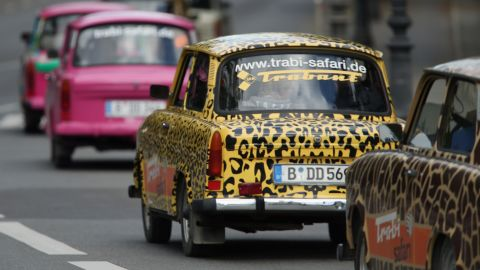 Tourists drive Trabant cars on a guided tour through the city center on September 19, 2013 in Berlin, Germany. Several companies now offer tours with the cars.