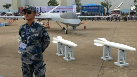 A guard stands by a Chinese-made drone at Airshow China on Tuesday, November 11.