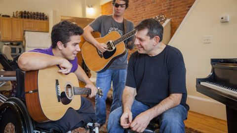 Arthur Bloom, right, rehearses with members of the MusiCorps Wounded Warrior Band at Bloom's home in Washington. Through his nonprofit, Bloom is using music to help hundreds of injured troops recover their lives.