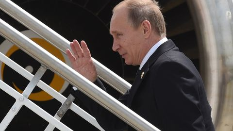 This handout photo taken and released by G20 Australia on November 16, 2014 shows Russias President Vladimir Putin (C) waving goodbye as he leaves the G20 Summit, at the airport in Brisbane. Putin jetted out of Australia after a testy G20 summit where he faced concerted Western fire over the Ukraine crisis, saying he left slightly early because he needed to get some sleep. AFP PHOTO / Steve Holland/ G20 Australia