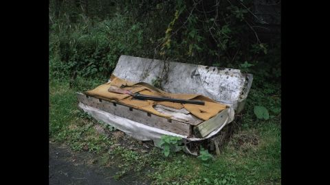 """A gun sits on a hermit's """"home"""" in Russia."""