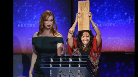"""CNN Hero Leela Hazzah, who is <a href=""""http://www.cnn.com/2014/11/24/world/gallery/cnn-heroes-leela-hazzah/index.html"""">helping to save lions</a> in Africa, holds up her award next to actress Christina Hendricks during the show."""