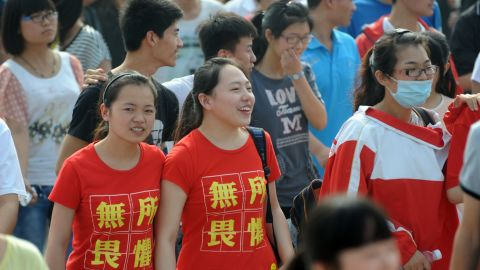 """Two students  wearing t-shirts saying """"fear nothing"""" walk into the exam room to sit the 2014 college entrance exam in China, or the 'gaokao', in Bozhou, east China's Anhui province. The """"gaokao"""" can make the difference between a prestigious university in Beijing or relegation to a regional college."""