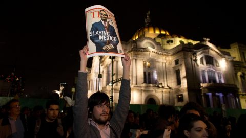 A protester holds up a poster parodying Pena Nieto during a rally in Mexico City on November 20.