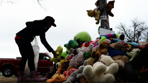 A wellwisher aranges stuffed toys on November 22, 2014 at a makeshift memorial where 18-year-old Michael Brown was shot dead by a police officer, in Ferguson, Missouri. Tensions rose on November 22 in the troubled St Louis suburb of Ferguson, with a grand jury poised to decide whether to prosecute a white police officer for killing an unarmed black teenager. US President Barack Obama has called for calm, Missouri's governor declared a state of emergency and activated the state National Guard, and the FBI has deployed an extra 100 personnel in the city.Police helicopters trained search lights over Ferguson late Friday as a small gaggle of protesters braved the cold to demand that officer Darren Wilson stand trial for shooting 18-year-old Michael Brown on August 9. AFP PHOTO/Jewel Samad (Photo credit should read JEWEL SAMAD/AFP/Getty Images)