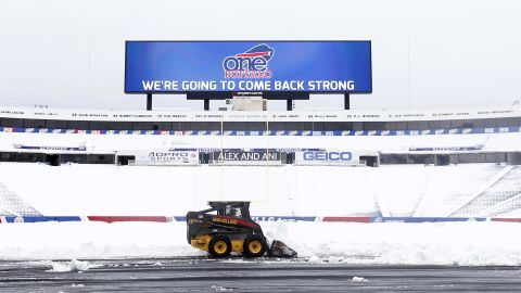 """Workers clear snow from the field at Ralph Wilson Stadium on Sunday, Nov. 23, 2014, in Orchard Park, N.Y. Snowed out today at the stadium, the Bills are in Detroit to play their """"home"""" NFL football game against the New York Jets on Monday night, Nov. 24, 2014. (AP Photo/Mike Groll)"""