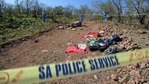 A forensics team searches the area around the body of a poached rhino looking for clues. The rhino was shot along Kruger National Park's border with Mozambique. The investigators have had such a backlog of rhino poaching cases its taken them 10 days before they could get to this one.