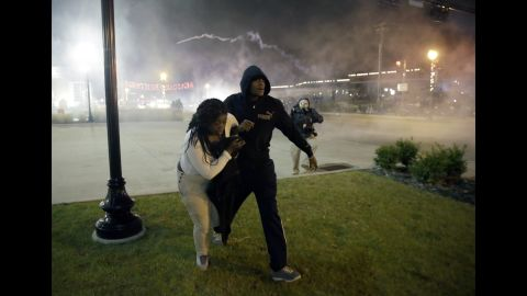 Protesters run for shelter as smoke fills the streets of Ferguson on November 24.
