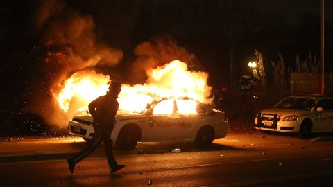 A police officer runs by a burning police car on November 24.