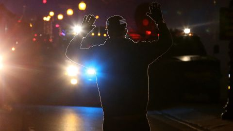 A protester stands in front of police vehicles with his hands up on November 24.