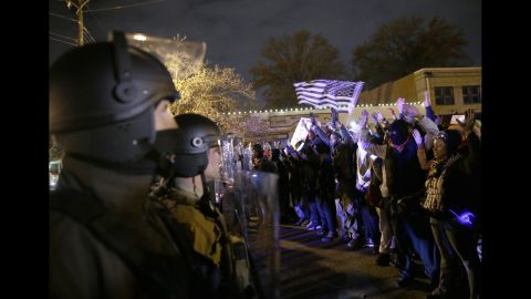 Police officers stand guard as protesters confront them on November 24.