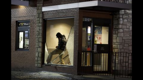 A man steps out of a vandalized store on November 24.