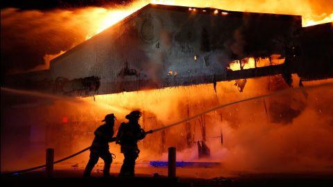 Firefighters work on extinguishing a Little Caesars restaurant on November 24.