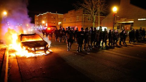 Police in riot gear move past a burning vehicle on November 24.