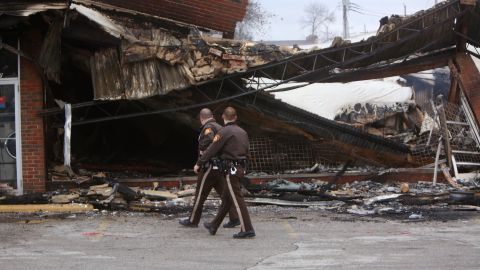 Police officers walk past the smoldering remains of a beauty supply store in Ferguson on Tuesday, November 25.